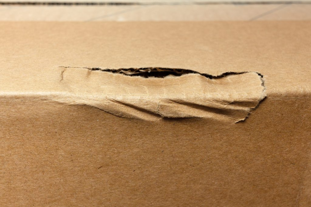 damaged rumpled edge of the cardboard box during delivery.