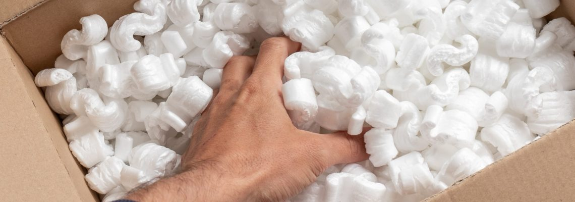 Cardboard box filled with packing styro foam pellets. hand reaching to search for fragile shipments. Packaging or online shopping ordering concept.