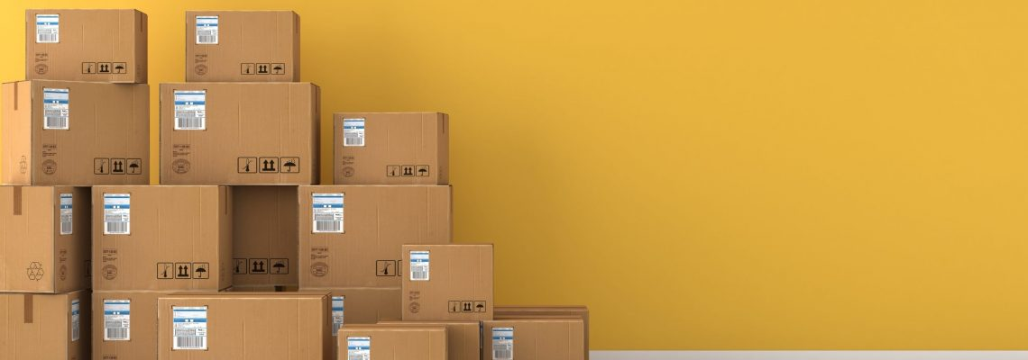 Moving boxes empty room in front of a yellow wall